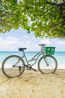 Samotny rower vintage z zielonym koszem na tropikalnej piaszczystej plaży, z niebem i spokojnym błękitnym morzem