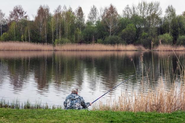 Samotny rybak na brzegu rzeki wczesnym rankiem lata na białorusi
