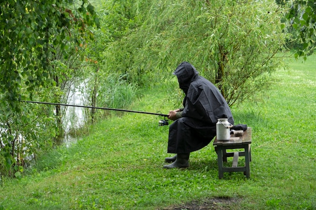 Samotny rybak na jeziorze w deszczową lato pogodę. rybak łowi ryby w płaszczu przeciwdeszczowym