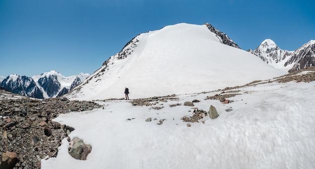 Samotny trekking w górach. mężczyzna wędrowców w dół górskiej ścieżki. w tle duże ośnieżone góry. kopiowanie miejsca, widok panoramiczny.