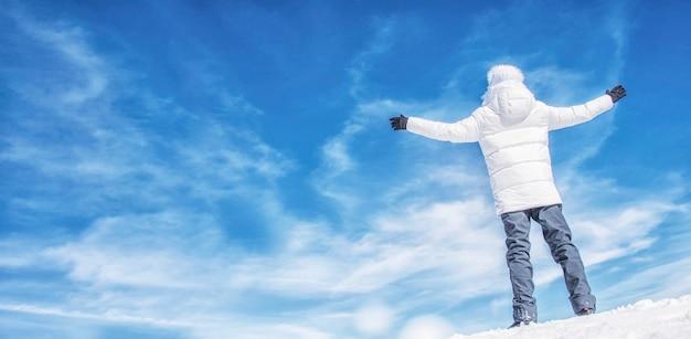 Samotny turysta stojący na zaśnieżonym szczycie góry w pozie zwycięzcy