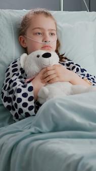 Samotny zmartwiony pacjent dziecko noszący rurkę nosową z tlenem, leżący w łóżku, trzymający pluszowego misia
