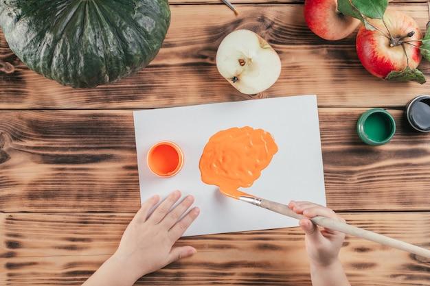 Samouczek halloweenowy samouczek z dyniowymi jabłkami krok po kroku. krok 5: ręce dziecka pędzlem pomarańczową farbą na papierze. widok z góry