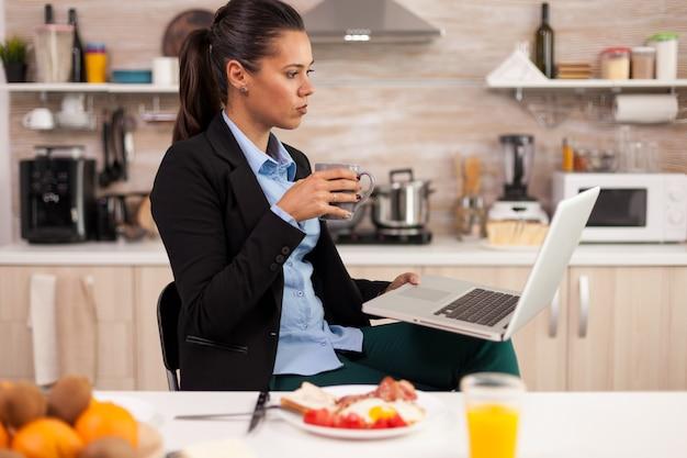 Samozatrudniony korzystający z laptopa w nowoczesnej kuchni i pijący kawę rano cup