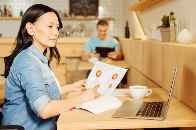 Samozatrudniony. piękna skoncentrowana ciemnowłosa niepełnosprawna kobieta siedzi na wózku inwalidzkim i pisze w swoim notatniku i pracuje na swoim laptopie oraz mężczyzna siedzący w tle