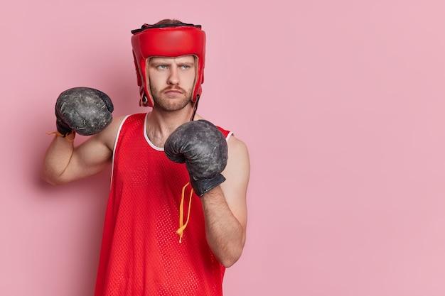 Samozwańczy sportowiec skoncentrował wzrok niezadowolony wzrok nosi rękawice bokserskie ćwiczy umiejętności walki wygląda poważnie na bok