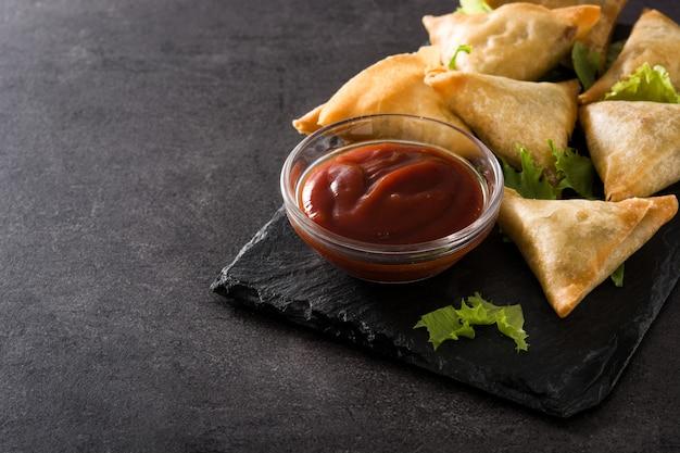 Samsa lub samosas z mięsem i warzywami na czarno. copyspace