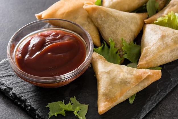 Samsa lub samosas z mięsem i warzywami na czarno. tradycyjne indyjskie jedzenie. ścieśniać