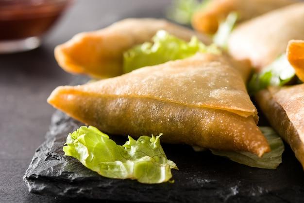 Samsa lub samosas z mięsem i warzywami na czarnym tle. tradycyjne indyjskie jedzenie. zbliżenie
