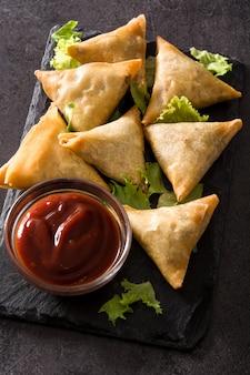 Samsa lub samosas z mięsem i warzywami na czarnym tle. tradycyjne indyjskie jedzenie.