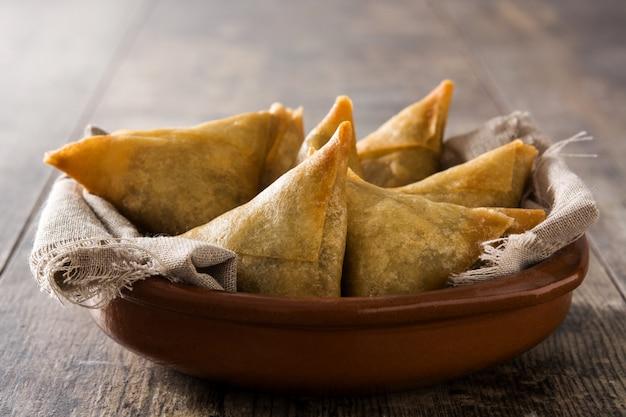 Samsa lub samosas z mięsem i warzywami w pucharze na drewnianym stole. tradycyjne indyjskie jedzenie