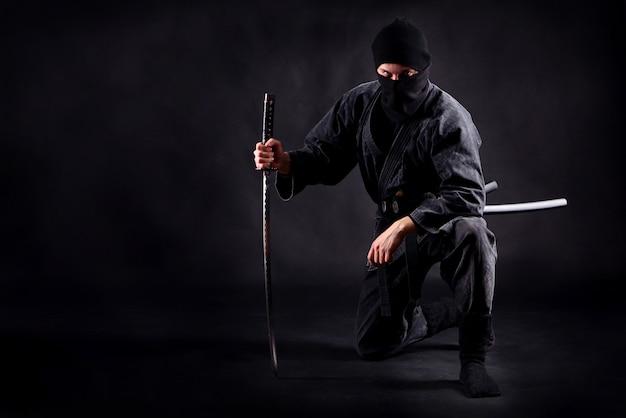 Samuraj ninja przykucnął na jednej nodze i oparty o miecz