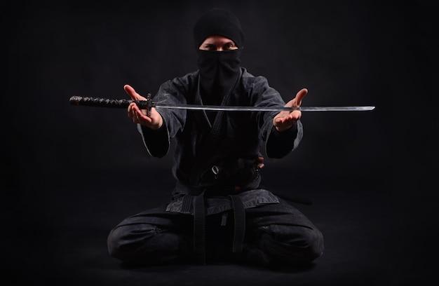 Samuraj ninja trzyma w rękach katanę