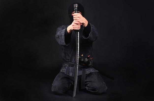 Samurajski wojownik ninja siedzi na kolanach i mieczem zakrywa twarz.