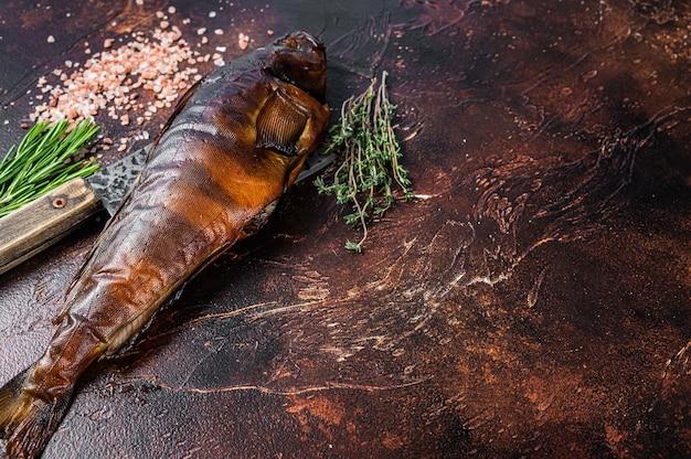 Sandacz wędzony na gorąco lub sandacz na drewnianej desce z ziołami. ciemne tło. widok z góry. skopiuj miejsce.
