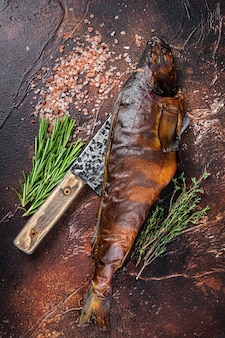Sandacz wędzony na gorąco lub sandacz na drewnianej desce z ziołami. ciemne tło. widok z góry.