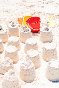 Sandcastle przy biel plażą z plastikowymi dzieciak zabawkami i dennym tłem