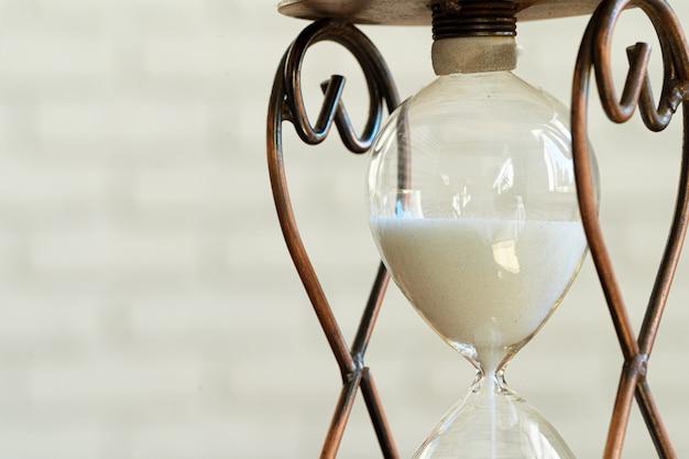 Sandglass na drewnianym zakończeniu up. pojęcie czasu