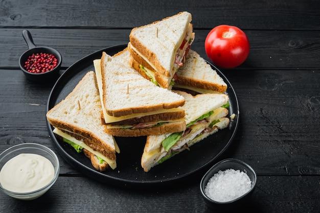 Sandwich chleb pomidor, sałata i żółty ser, na czarnym drewnianym stole