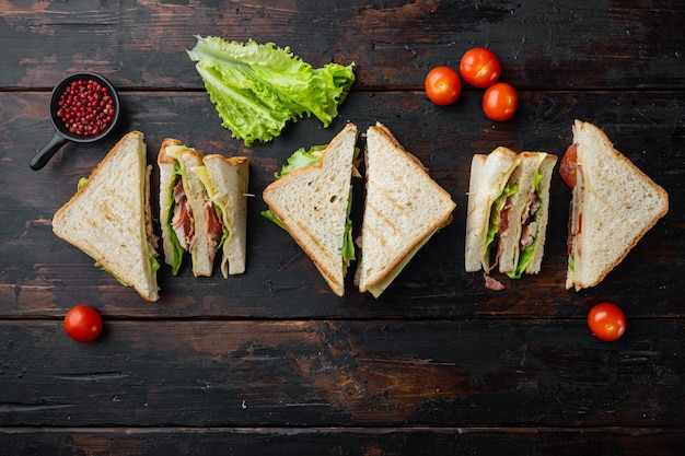 Sandwich chleb pomidor, sałata i żółty ser, na starym drewnianym stole, widok z góry