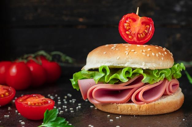 Sandwich kiełbasa burger sałata warzywa liściaste szynka salami, przekąska pomidorowa