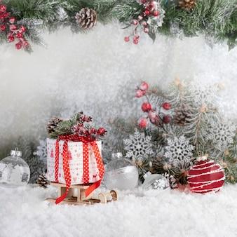 Sanie świętego mikołaja z prezentem świątecznym na śniegu z gałęziami jodły i bombkami. wesołych świąt i szczęśliwego nowego roku koncepcja.
