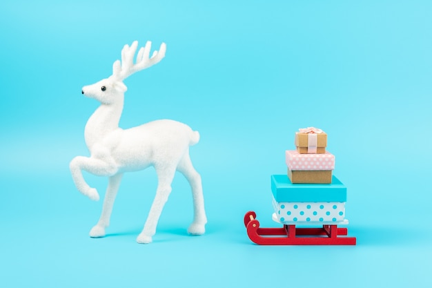 Sanie świętego mikołaja z pudełkami na prezenty i białym reniferem na niebiesko