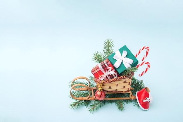 Sanie świętego mikołaja z pudełkami prezentowymi, słodyczami i ozdób choinkowych na gałęzie jodły na jasnoniebieskim tle. skopiuj miejsce.
