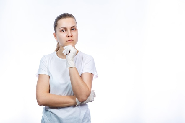 Sanitariusz dziewczyna zakłada białe rękawiczki medyczne na ręce. ochrona przed zarazkami i wirusami. jest w białej koszulce na białym tle.