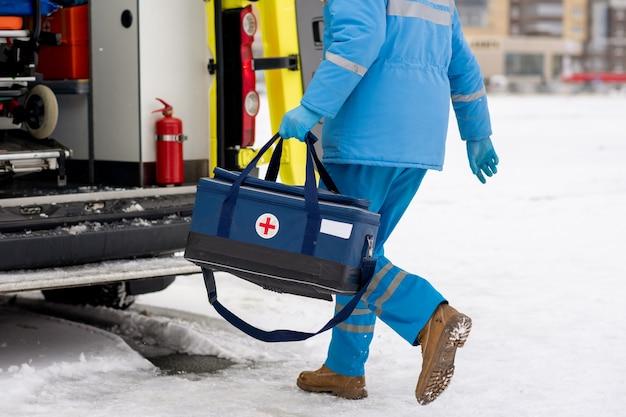 Sanitariusz mężczyzna w niebieskim ubraniu roboczym i rękawiczkach niosący apteczkę z czerwonym krzyżem podczas wsiadania do samochodu pogotowia ratunkowego