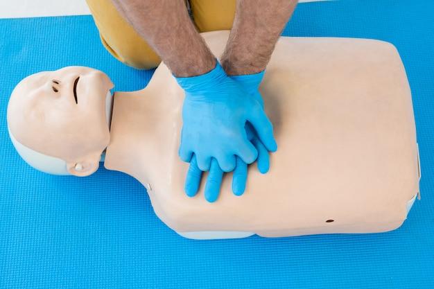 Sanitariusz praktykujący resuscytację krążeniowo-oddechową na manekinie