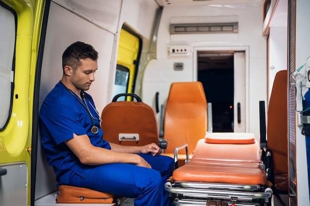 Sanitariusz w niebieskim mundurze siedzący w karetce i myślący o czymś.