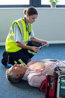 Sanitariusz za pomocą zewnętrznego defibrylatora podczas resuscytacji krążeniowo-oddechowej