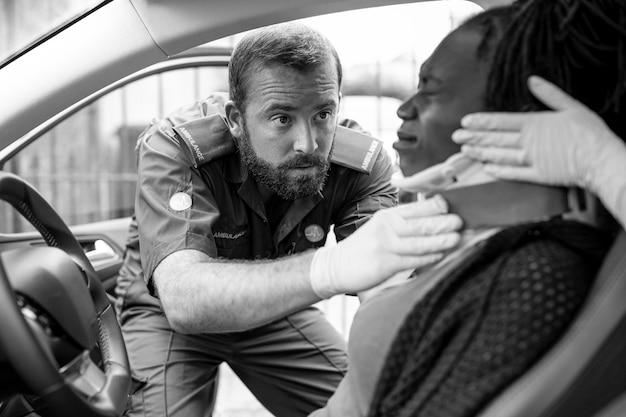 Sanitariusz zakłada kołnierz szyjny rannej kobiecie po wypadku samochodowym