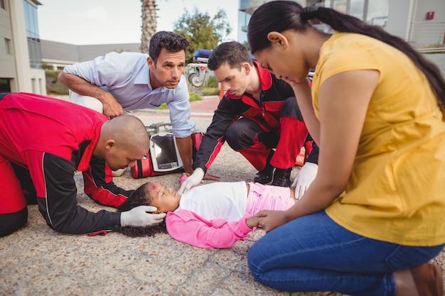 Sanitariusze badający ranną dziewczynę