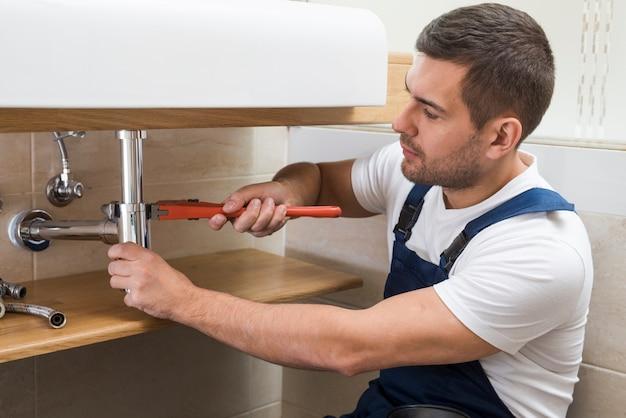 Sanitarny technik używa klucz na zlew