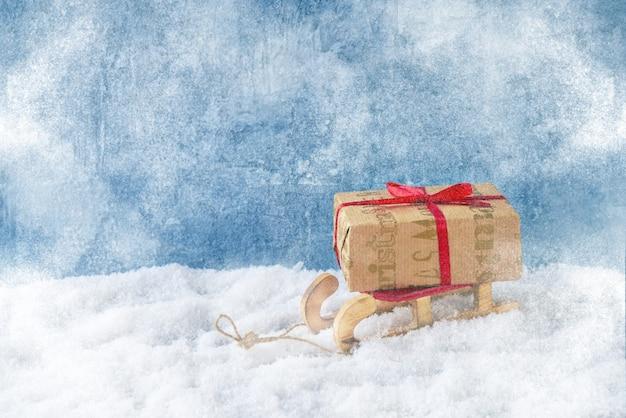 Sanki z prezentem na śniegu. skopiuj miejsce