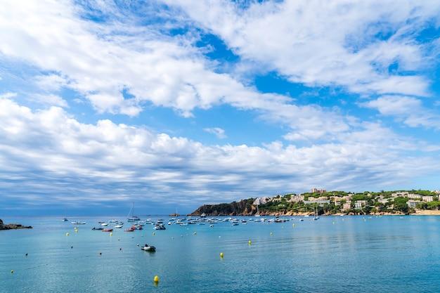 Sant pol plaża z łodziami na morzu w ciągu dnia z białymi chmurami.