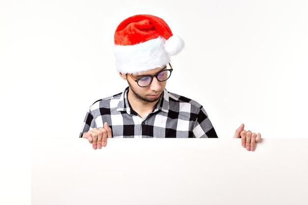 Santa brodaty mężczyzna, brutalny hipster z wąsami na zdziwionej twarzy w boże narodzenie czerwony kapelusz na święta nowego roku z arkuszem białej księgi na białym tle, miejsce.