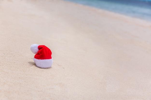 Santa christmas hat w piasku na tropikalnej plaży. letni zwrotnik wakacyjny