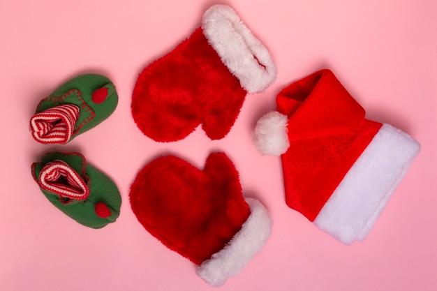 Santa claus czapki, rękawiczki i skarpetki makieta na różowym tle. świąteczna płaska makieta, widok z góry z bliska