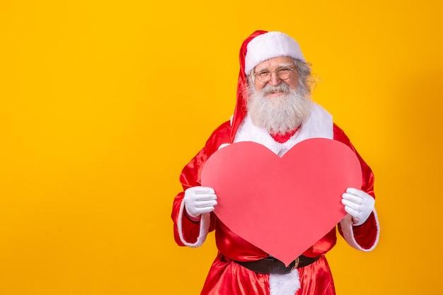 Santa claus gospodarstwa duże czerwone serce karty w żółtym tle. romantyczny święty mikołaj.