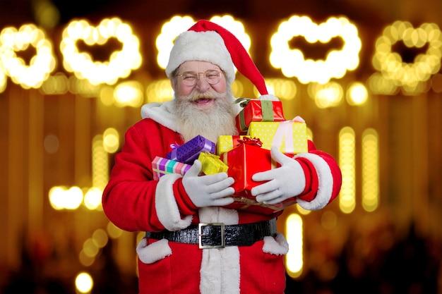 Santa claus gospodarstwa pudełka z prezentami.