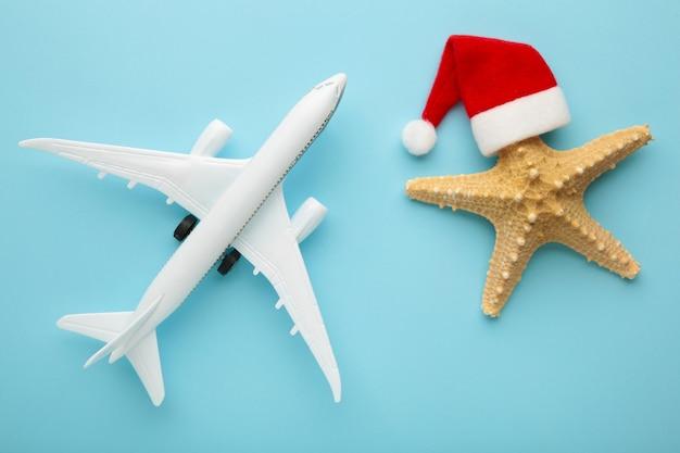 Santa claus kapelusz na rozgwiazdy i biały samolot na niebieskim tle.