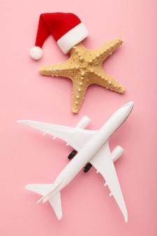 Santa claus kapelusz na rozgwiazdy i biały samolot na różowym tle.