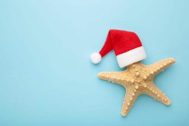 Santa claus kapelusz na rozgwiazdy na niebieskim tle. zimowe powołanie