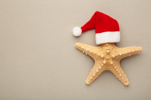 Santa claus kapelusz na rozgwiazdy na szarym tle. zimowe powołanie