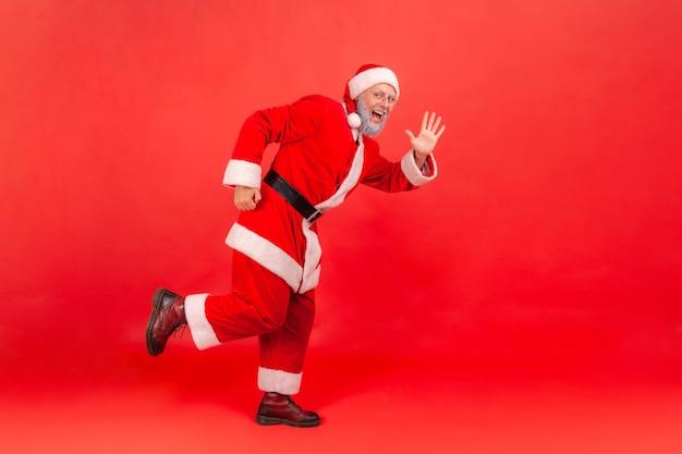 Santa claus stojący patrząc na powitanie kamery i machając ręką i zaskoczony.