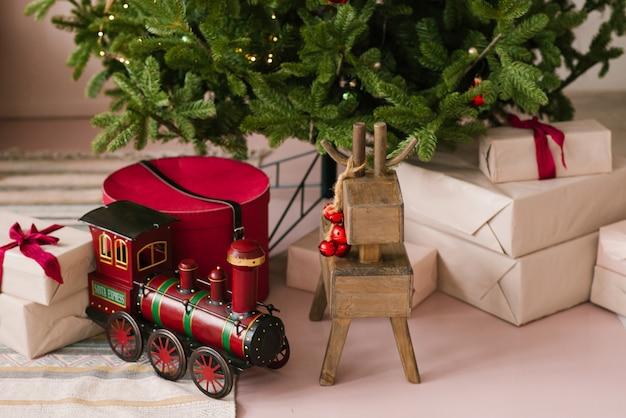 Santa claus toy express, drewniana zabawka z jelenia i prezenty świąteczne pod choinką