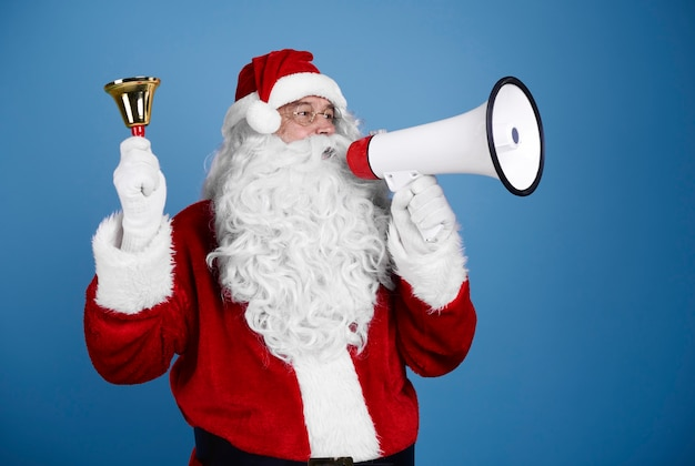 Santa claus z handbell krzycząc do megafonu